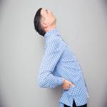 Man having a back pain over gray background